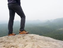 Male legs in dark hiking trousers and leather trekking shoes on peak of rock above  misty valley. Outline of hill. Side on horizon, Sun hidden in misty clouds Stock Images