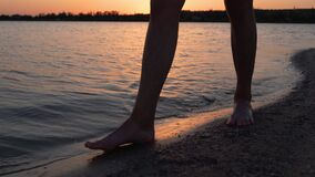 Male legs and feet walking along lake or pond on sandy beach in the dusk. Men move on shore alone. Calm water on