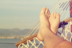 Male legs in a hammock on the beach against the sea in a summer sunny day. Stock Images