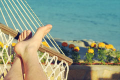 Male legs in a hammock on the beach against the sea in a summer sunny day. Holiday by the sea Stock Image