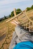 Male legs in a hammock. Man in a hammock in the garden, man in hammock on a sunny day Royalty Free Stock Photos