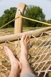 Male legs in a hammock. Man in a hammock in the garden, man in hammock on a sunny day Royalty Free Stock Images