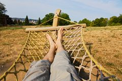 Male legs in a hammock. Man in a hammock in the garden, man in hammock on a sunny day Stock Images