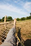 Male legs in a hammock. Man in a hammock in the garden, man in hammock on a sunny day Stock Photos