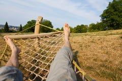 Male legs in a hammock. Man in a hammock in the garden, man in hammock on a sunny day Royalty Free Stock Photography