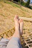 Male legs in a hammock. Man in a hammock in the garden, man in hammock on a sunny day Stock Image