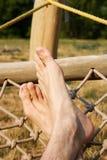 Male legs in a hammock. Man in a hammock in the garden, man in hammock on a sunny day Stock Photo