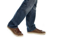 Male legs in jeans and brown sneakers shoes. Make step  in white background Royalty Free Stock Photos