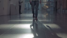 Male legs in jeans move to the camera along the corridor with artificial lighting. Close-up of the male legs in jeans move to the camera along the corridor with stock video footage