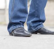 Male legs in jeans and shoes. In the park in nature Stock Photos