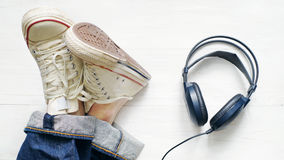 Male legs in jeans and sneakers, black earphones. On a white wooden surface, top view Stock Photo