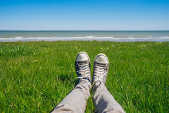 Male legs in jeans and sneakers on fresh grass against seacoast. Sunny summer day Royalty Free Stock Photos