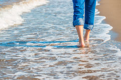 Male legs in jeans walking along the seashore Stock Photo