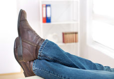 Male legs on office desk. Close up of male legs in jeans and with brown ankle shoes on feet on office desk Royalty Free Stock Photo