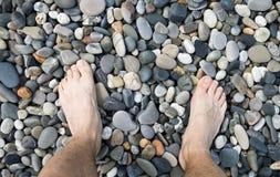 Male legs on pebble. Russia, coast of Black Sea, Sochi, Adler Royalty Free Stock Image