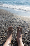 Male legs on the pebble coast of sea. Selective focus Stock Photography