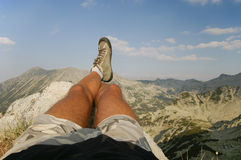 Male Legs Relaxing at the Summit Stock Images