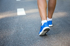 Male legs in running shoes outside on road. Male legs in running shoes outside on asphalt road Royalty Free Stock Images