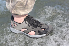 Male legs in sandals for rafting on ice of the river. Male leg in sandals for rafting on ice of the thawing river Stock Images