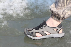 Male legs in sandals for rafting on ice of the river. Male leg in sandals for rafting on ice of the thawing river Stock Photo