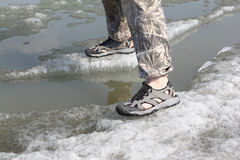 Male legs in sandals for rafting on ice of the river. Male legs in sandals for rafting on ice of the thawing river Stock Photography