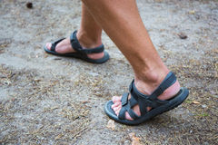 Male legs in sandals walking on road. Male legs in sandals walking on forest road Royalty Free Stock Images