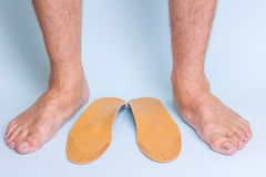 Male legs with signs of flat feet and joints and orthopedic insoles on a blue background. Front view. stock photos