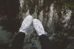 Male legs in sneakers against water with reflection of trees. Male legs in sneakers against water surface. Autumnal trees reflection. Fall concept Royalty Free Stock Images