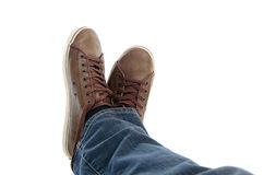 Male legs in sneakers and jeans lying. Male legs in brown shoes sneakers and jeans lying down on the grownd isolated on white background Stock Photos