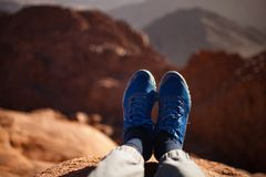 Male legs in sneakers over cliff against backdrop of mountain. Male legs in blue sneakers lit by sun over cliff against backdrop of mountain range Royalty Free Stock Image