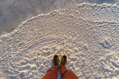 Male legs standing on scenic icy surface. Male legs standing on icy surface, pov shot stock photography