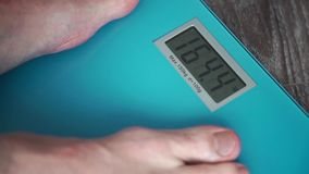 Male legs standing On A home floor scales. Standing On A Weighing Machine stock footage