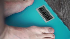 Male legs standing home floor scales on display ALARM. Standing On home floor scales stock video