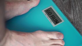 Male legs standing On A home floor scales on display GO RUN. Standing On A home floor scales stock video footage