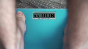 Male legs standing On A home floor scales and sees GO RUN. Standing On A Weighing Machine stock video footage