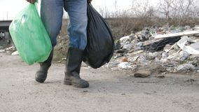 Male legs walking at garbage dump with trash bags stock footage