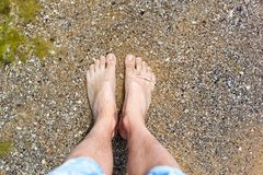 Male legs in the water on the sand beach view from above. Travel Tourist Vacation Stock Photo
