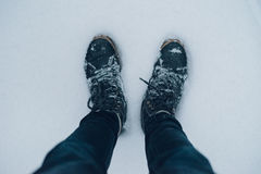 Male legs in winter boots on snowy surface. Top view with selective focus Royalty Free Stock Photography
