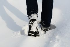 Male legs in winter shoes walking on snow covered path. Close -up. Male legs in winter shoes walking on snow covered path . Close -up Royalty Free Stock Images