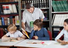 Male Librarian Showing Book To Schoolboy. Mature male librarian showing book to little schoolboy in library Royalty Free Stock Photos