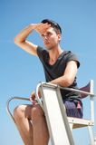Male life guard sitting on chair on a summer day Royalty Free Stock Photography