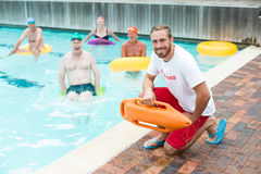 Male lifeguard crouching while swimmers swimming in pool Stock Images