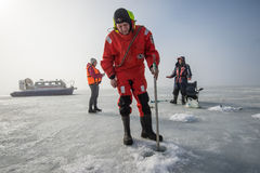 Male lifeguard measures the ice thickness. Saint-Petersburg, Russia - March 27, 2016: A member of the rescue team checks the thickness of the ice in the Gulf of Royalty Free Stock Photos