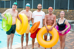 Male lifeguard with senior swimmers standing at poolside Royalty Free Stock Images