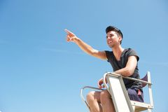 Male lifeguard smiling and pointing into the distance Royalty Free Stock Photography