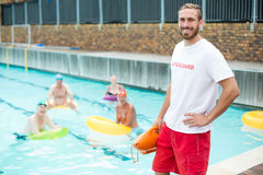 Male lifeguard standing while swimmers swimming in pool. Portrait of male lifeguard standing while swimmers swimming in pool Royalty Free Stock Photos