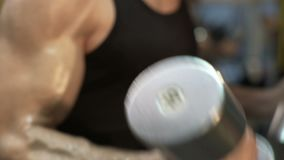 Male lifting heavy dumbbells with both hands simultaneously, close-up of arms. Stock footage stock video
