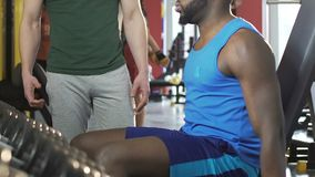 Male lifting up dumbbell with friend supporting aside, high-five to each other. Stock footage stock video footage