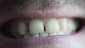 Male lips macro shooting. Close-up of a male mouth. He smiles and shows big teeth. There is light stubble on the man is face stock video footage