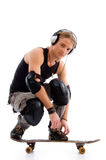 Male listening to music on skate board. With white background Stock Photography